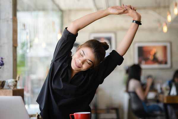 woman stretching her back when sitting at a cafe